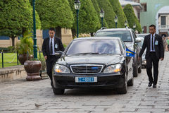 Bodyguards protect state automobile, which moves in the Grand Palace in Bangkok. Thailand Royalty Free Stock Photography