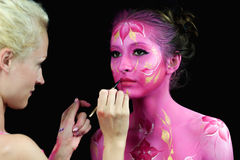 Bodypaint master in work, paints a model for a photo shoot. On black background Royalty Free Stock Photos