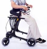 Bodypart della donna anziana che si siede sul camminatore fotografia stock libera da diritti
