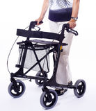 Bodypart of senior woman with modern walker. Lower bodypart of senior woman with happy expression in face with a modern walker for handicapped people isolated on Royalty Free Stock Image