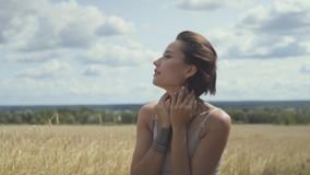 Bodysuit прелестной женщины нося с короткими волосами идя через пшеничное поле смотря вокруг Уверенная беспечальная девушка акции видеоматериалы