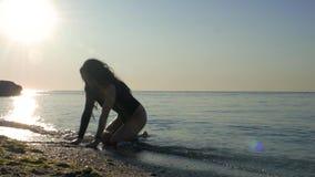 Bodysuit met een sportief lichaam dat yoga zijnd in het water door het overzees maakt Fitness, sport, yoga en gezond levensstijlc stock videobeelden