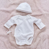 Bodysuit near a hat and a pacifier for babies Royalty Free Stock Photo