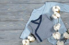 2 bodysuits голубых младенцев на серой деревянной предпосылке Мамы покупок Стоковое Изображение RF