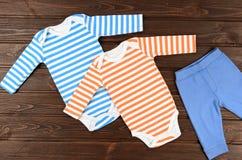Bodysuits и брюки младенцев на деревянной предпосылке Одежды младенца стоковое изображение