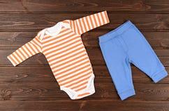 Bodysuits и брюки младенцев на деревянной предпосылке Стоковое фото RF
