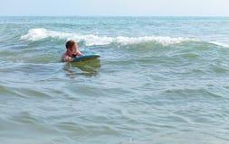 Bodysurfing - маленькая девочка занимаясь серфингом в Средиземном море, Испании Стоковое Фото