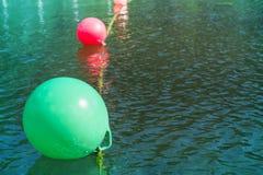 Boe multicolori su piccola acqua ondulata scura segnale di pericolo per i nuotatori Fotografie Stock Libere da Diritti