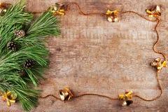 Boże Narodzenia obramiają od gałęziastych i złocistych dzwonów na drewnianym tle Zdjęcie Royalty Free