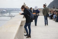 Boedapest, Hongarije - April 10, 2018: De jonge geconcentreerde vrouwen bekijkt het mobiele telefoonscherm stock afbeelding