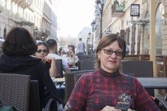 Boedapest, Hongarije - April 9, 2018: een vrouwenzitting op middelbare leeftijd op terras die van koffie alleen en zonnige camera stock fotografie