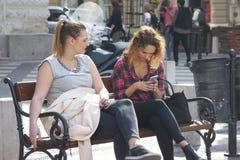 Boedapest, Hongarije - April 5, 2018: Twee Jonge Vrouwen op een Bank bij Park royalty-vrije stock afbeeldingen