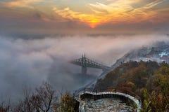 Boedapest, Hongarije - de Geheimzinnige mistige zonsopgang met Liberty Bridge Szabadsag verborg en vooruitzicht op Gellert-Heuvel royalty-vrije stock foto's