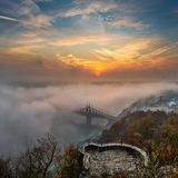 Boedapest, Hongarije - de Geheimzinnige mistige zonsopgang met Liberty Bridge Szabadsag verborg en vooruitzicht op Gellert-Heuvel stock afbeeldingen
