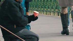Boedapest, Hongarije - December 6, 2018: Een hongerige bedelaarsvrouw zit op haar overlapping naast een riet en bedelt voor de aa stock footage