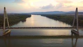 Boedapest, Hongarije - 4K hyperlapse vliegend boven Megyeri-Brug bij zonsondergang stock videobeelden