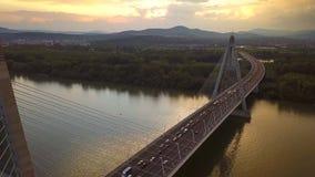 Boedapest, Hongarije - 4K vliegend boven Megyeri-Brug bij zonsondergang met zwaar middagverkeer stock videobeelden
