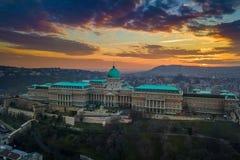 Boedapest, Hongarije - Luchtpanorama van beroemd Buda Castle Royal Palace bij zonsondergang met verbazende kleurrijke hemel royalty-vrije stock fotografie