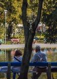 Boedapest, Hongarije, 13 September, 2019 - Bejaard paar die van de dag voor een meer genieten bij varolisgetpark royalty-vrije stock foto's