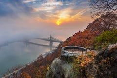 Boedapest, Hongarije - Vooruitzicht op Gellert-Heuvel met Liberty Bridge Szabadsag Hid, mist over Rivier Donau, kleurrijke hemel  royalty-vrije stock afbeelding