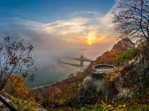 Boedapest, Hongarije - Vooruitzicht op Gellert-Heuvel met Liberty Bridge Szabadsag Hid, mist over Rivier Donau, kleurrijke hemel  stock foto