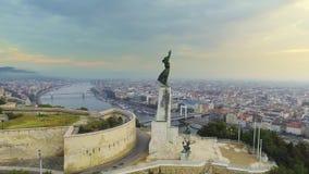 Boedapest, Hongarije - Zonsopgang, Luchtlengte door het vrijheidsstandbeeld en mening van de vroege zon over de stad stock footage