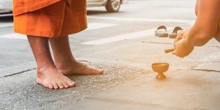 Boeddhistisch aanbiedingsvoedsel aan de monniken om aalmoes aan de monniken te geven en water te gieten Stock Fotografie