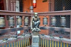 Boeddhistisch gebedwielen en aapstandbeeld Stock Foto's