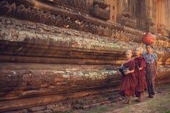 Boeddhistische beginnermonniken die aalmoes lopen stock foto's