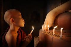 Boeddhistische beginners die met kaarslicht in tempel bidden Stock Foto