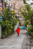 Boeddhistische monnik die oranje robes dragen en smalle straat lopen stock afbeeldingen
