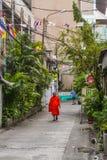 Boeddhistische monnik die oranje robes dragen en smalle straat lopen stock afbeelding