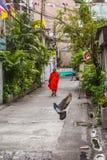 Boeddhistische monnik die oranje robes dragen en smalle straat lopen royalty-vrije stock afbeeldingen