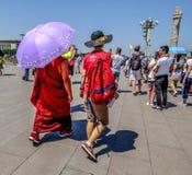 Boeddhistische monnik en Chinese mens die in Tienanmen-Vierkant in China lopen stock foto's