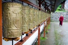 Boeddhistische monnik en gebedwielen in een rij Stock Afbeeldingen