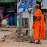Boeddhistische monnik in oranje robes dichtbij een reclamebanner op de straat stock foto