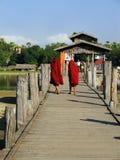 Boeddhistische monniken die op de brug van U Bein, Amarapura, Myanmar lopen Royalty-vrije Stock Foto's