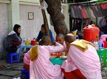 Boeddhistische nonnen die snacks op straat eten stock foto
