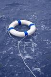 Boei, lifebelt, lifesaver drijvend in oceaan als hulpmateriaal Stock Afbeeldingen