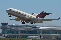 Boeing 727 Take off. 40 year old Boeing 727 takes off with a modern airport terminal in the background. This aircraft owner is Peter Getty Gordon, fourth son of Royalty Free Stock Image