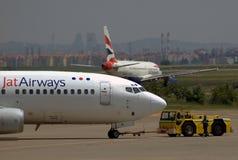 BOEING 737-300 avec le camion de remorquage et l'AIRBUS A-319 Photographie stock libre de droits