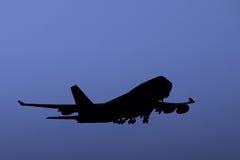 Boeing 747 jumbo jet taking off at dusk. Stock Images