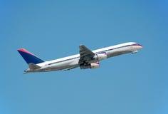 Boeing 757 passenger jet. Passenger jetliner in flight after takeoff against blue sky Stock Image