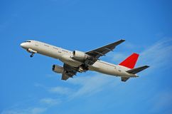 Boeing 757 passenger jet taking off. Side view of modern passenger jet airplane in flight stock image
