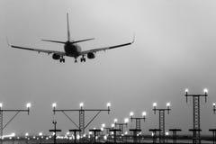 Boeing 767 atterrissant avec des lumières de piste en fonction. Photo stock
