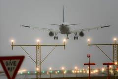 Boeing 767 atterrissant avec des lumières de piste en fonction. image stock