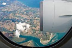 Boeing 777 window. Boeing 777 reaching England coast Royalty Free Stock Photos