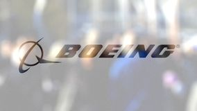 Boeing Company logo on a glass against blurred crowd on the steet. Editorial 3D rendering