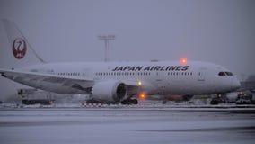 Boeing 787-8 Dreamliner de Japan Airlines sous des chutes de neige à l'aéroport clips vidéos