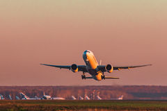 Boeing 777-300er Emirates Airlines takes off at sunset Stock Images